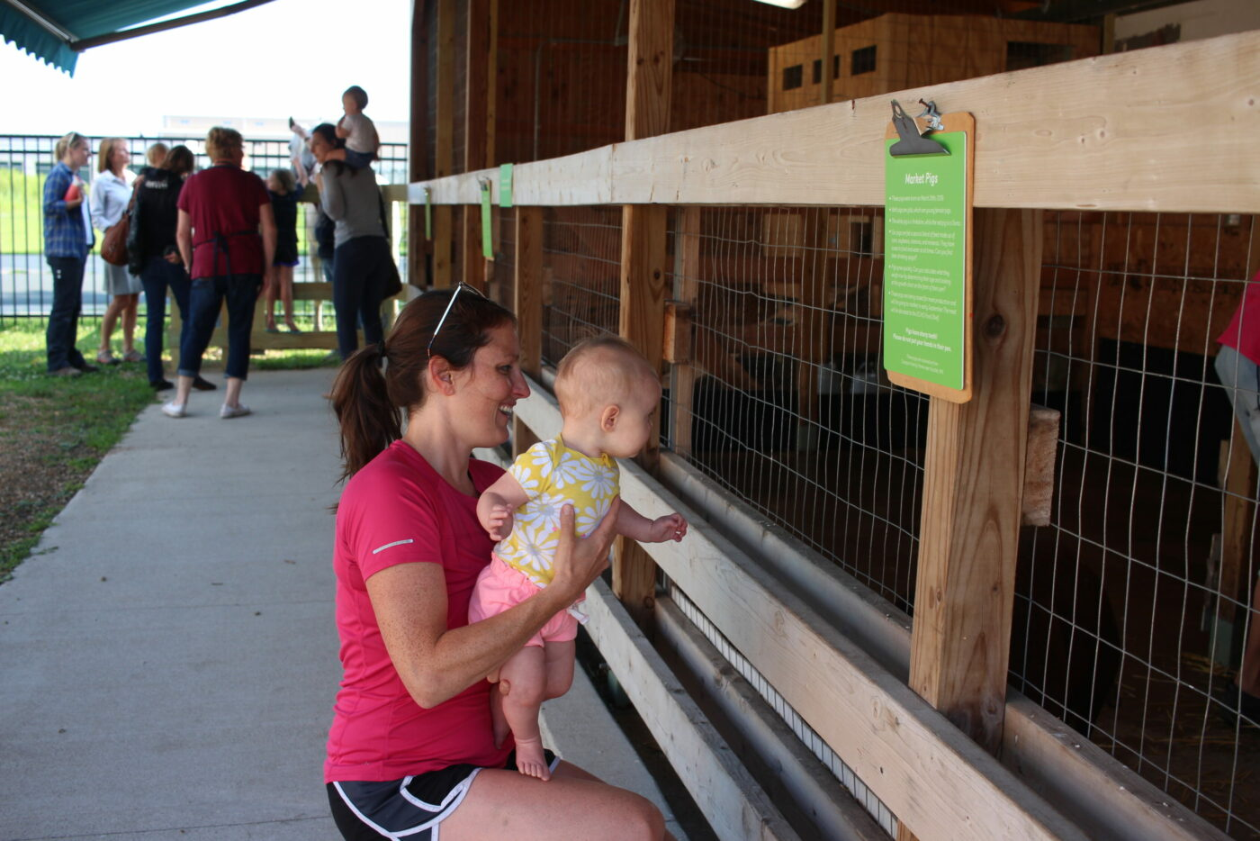 Baby and Parent learning about Pigs in the Alltech Farmyard at the Children's Museum of Southern Minnesota in Mankato