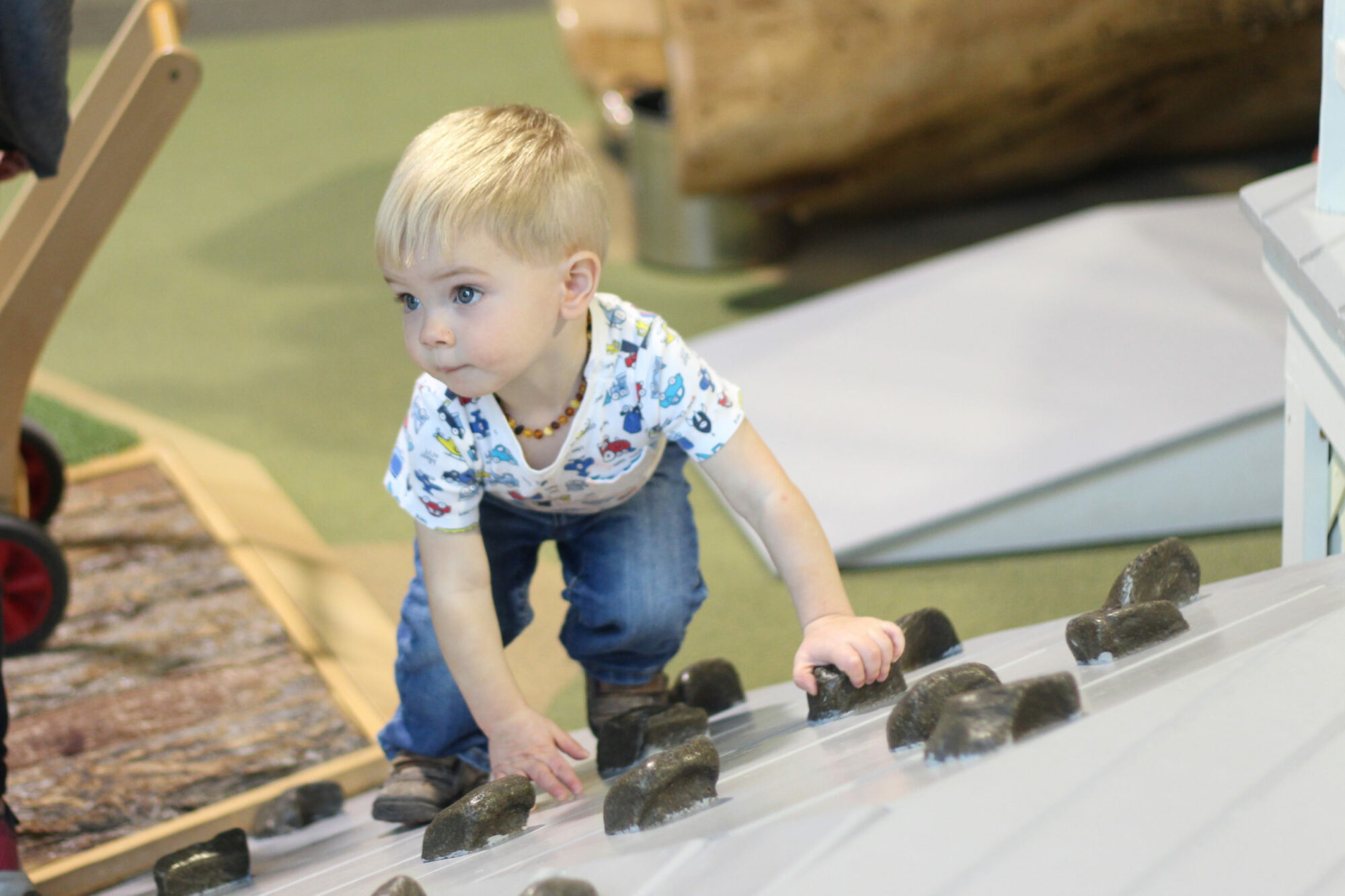 Toddler climbing in the play porch children's museum mankato