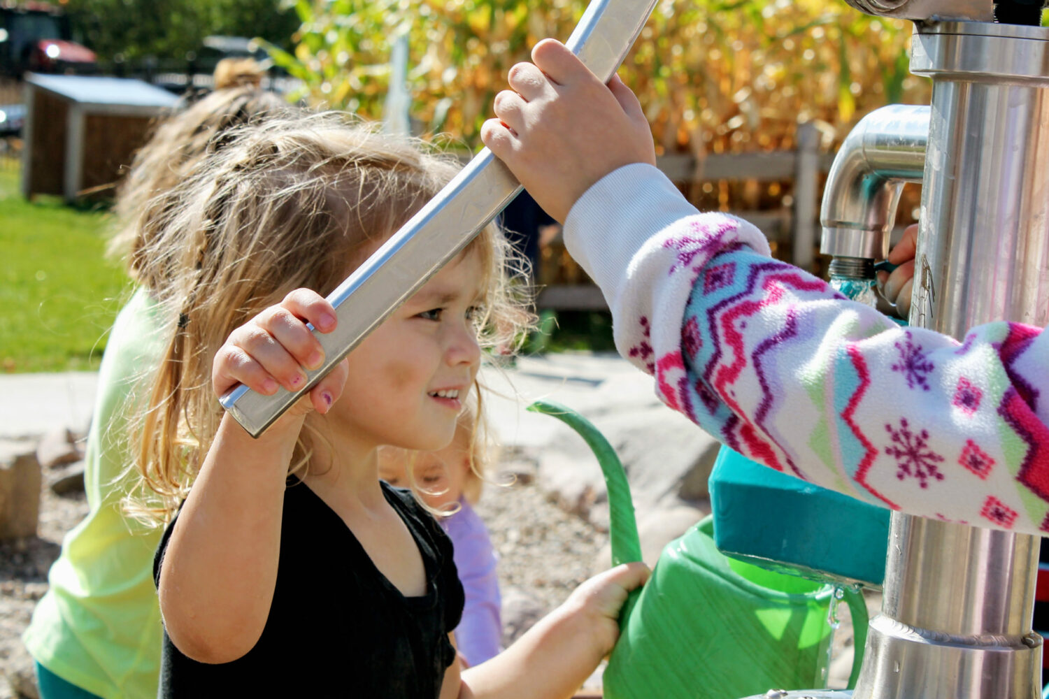 Child-pumping-water-pump-water-play-outdoor-nature-play-area-Dotson-Back-40-Alltech-Farmyard-Childrens-Museum-of-Southern-Minnesota