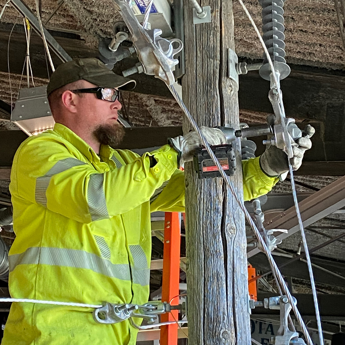 A volunteer installs the power pole in the Energy: Powered by Play Exhibit